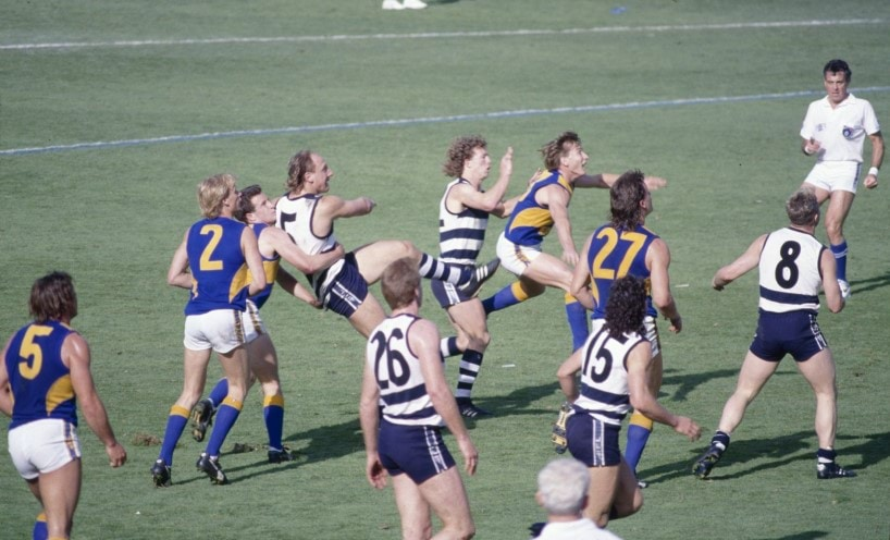 Geelong and West Coast football players on field during a game, by Rennie Ellis
